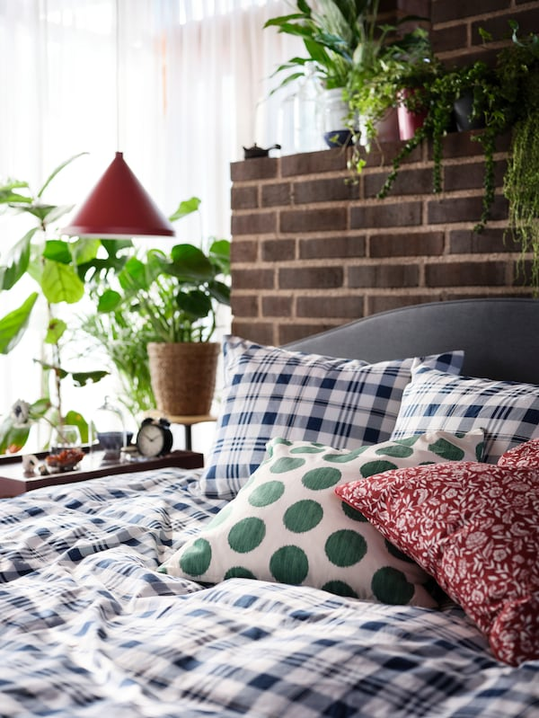 SPIKVALLMO bed linen with white-blue checks, a red-white cushion, a white-green cushion, and green plants in the background.