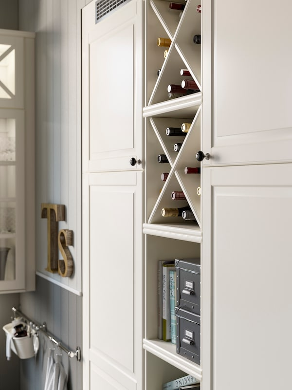 White shelves with white wine shelf inserts used to store wine bottles. Cookbooks and boxes are on the shelves below.