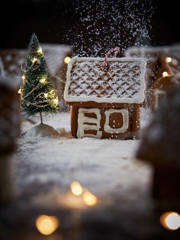 Una casa de pan de jengibre VINTERSAGA en miniatura decorada y una guirnalda luminosa VISSVASS sobre las que cae una nevada de azúcar glas.