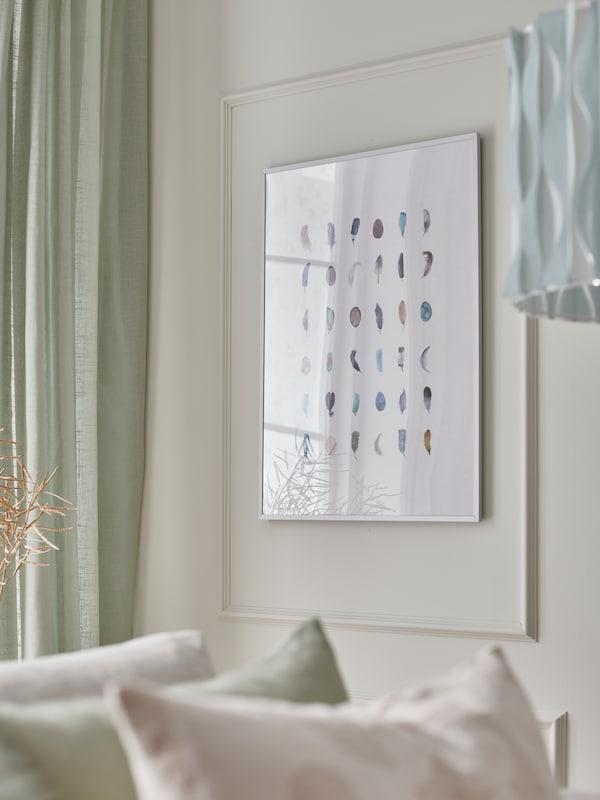 Et BILD bilde med fargerike fjær i en sølvfarget LOMVIKEN ramme henger på en kremfarget vegg i ei lys stue.