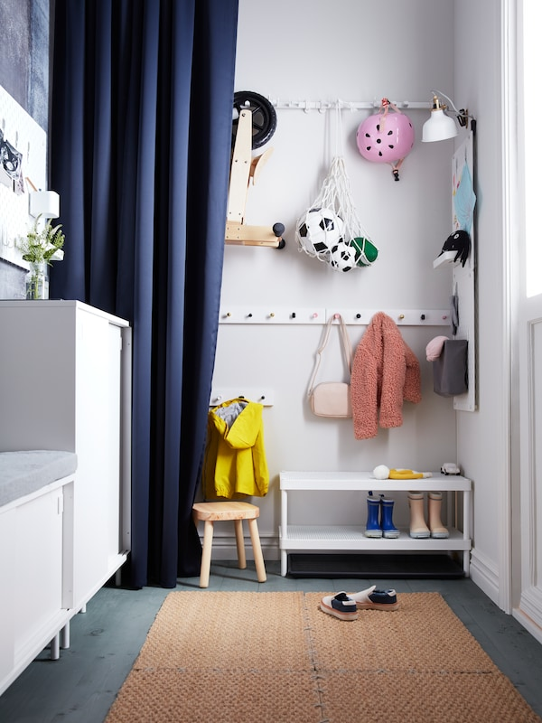 A narrow hallway with a MAJGULL curtain by rows of hooks holding children's play equipment and clothing above a shoe rack.