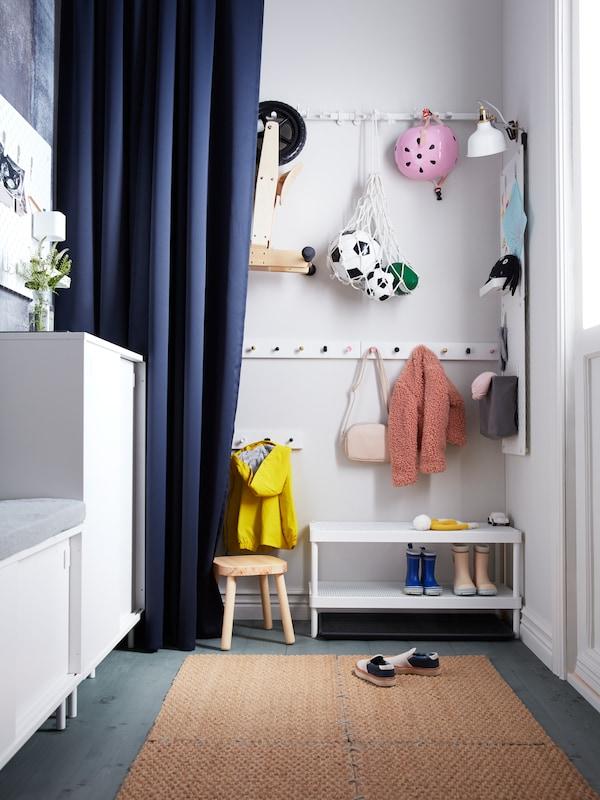 Unha entrada estreita cunha cortina MAJGULL a carón de ganchos nos que hai xogos infantís e roupa, situados enriba dun estante zapateiro.