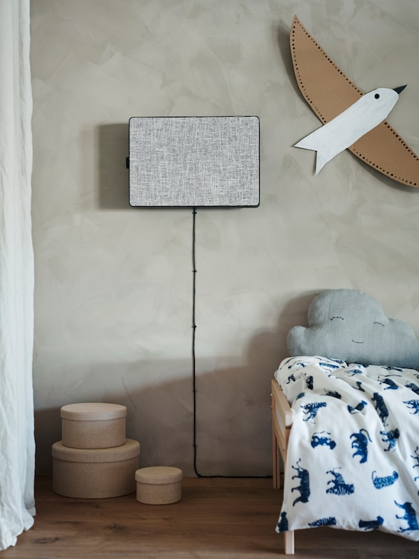 A black and grey FÖRNUFTIG air purifier hangs on a grey wall above a child's bed, next to a paper bird.