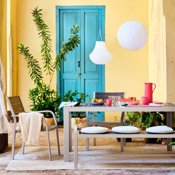 Ein mit Tassen und Untertassen, Gläsern und Grünpflanzen gedeckter Tisch im Freien, dazu Stühle.