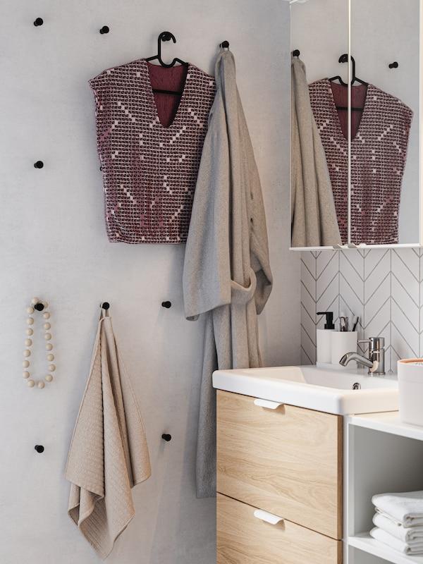 Conxunto de ganchos negros colocados dun xeito gráfico na parede do cuarto de baño, cunha toalla, un albornoz, unha blusa e un colar.