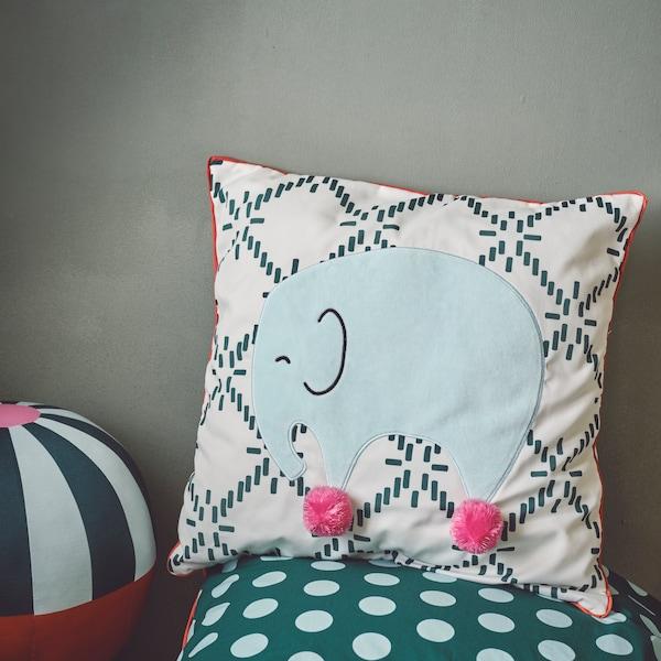 Un coussin à motifs verts et blancs, avec un éléphant dessus, ajoutera de superbes accents bohèmes à toute chambre d'enfant.