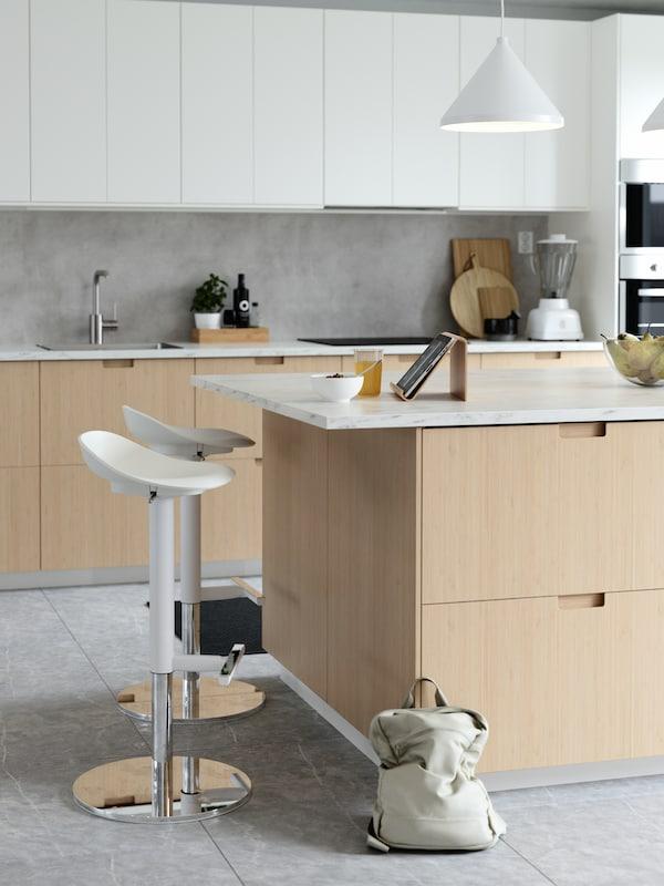 Kjøkkenøy med trefronter, to hvite barkrakker, et nettbrett og snacks på benkeplata og en beige ryggsekk.