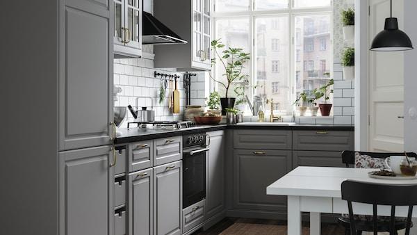 Graue BODBYN / METOD Küche in L-Form mit schwarzen Elektrogeräten. Im Vordergrund sieht man enen weißen Esstisch mit schwarzen Stühlen.