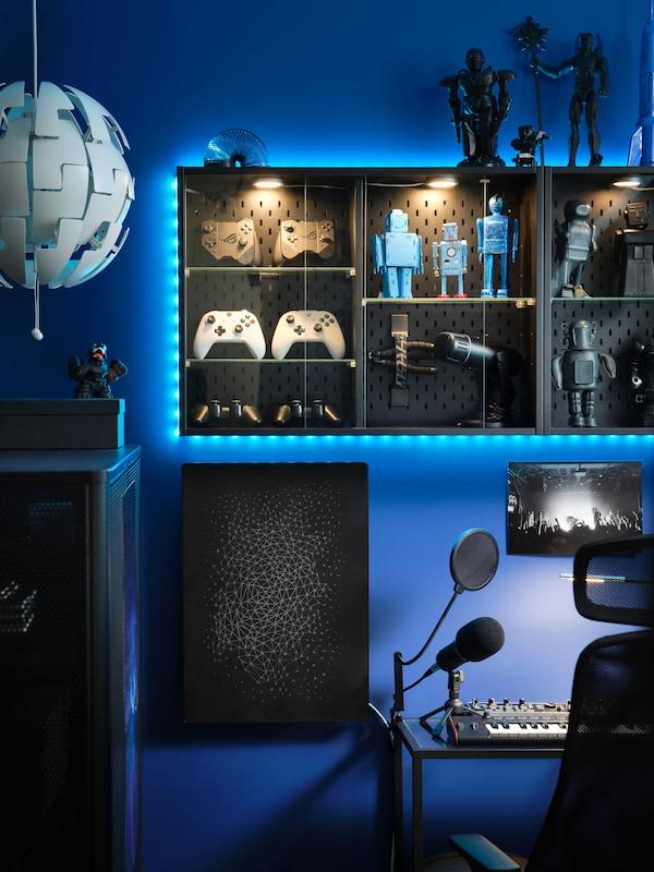 Et rum med en reol omringet af blot lys fyldt med figurer og gamingudstyr.