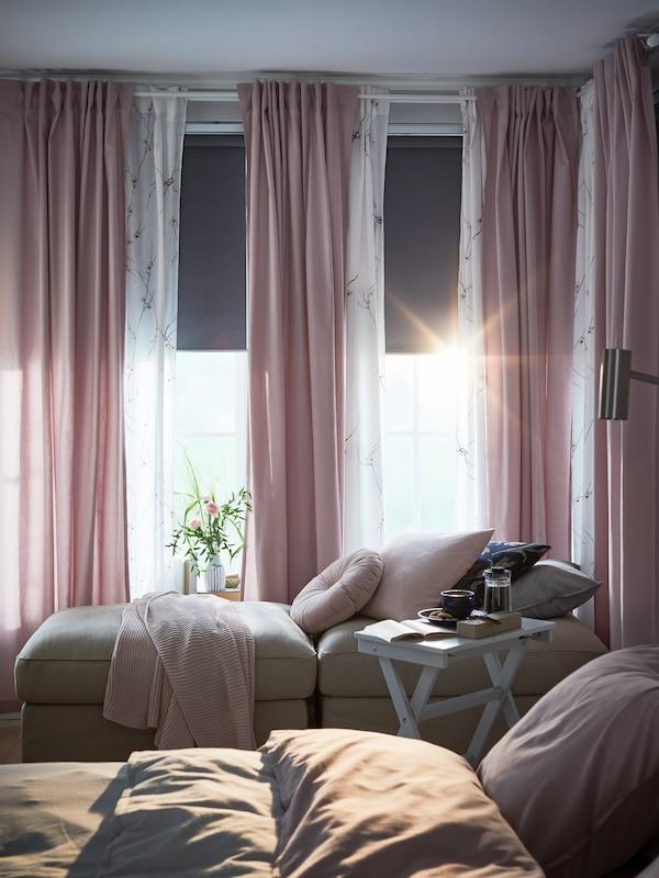 Grå mørklægningsrullegardiner, der er rullet halvt ned, tynde, lyserøde og hvide gardiner, sofamoduler ved vinduet og et hvidt bakkebord.
