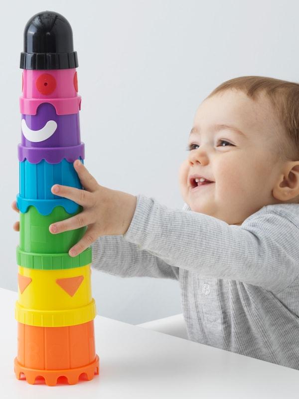 Egy mosolygós baba ül egy etetőszékben, az asztalon egy élénk színű MULA poharakból épített toronyba kapaszkodik.