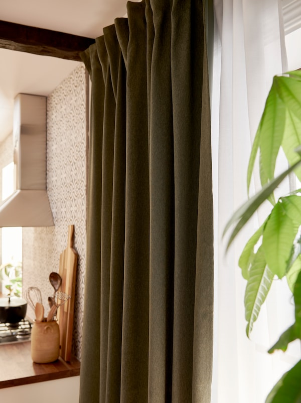 A green BLÅHUVA block-out curtain and a light curtain hang in a window outside a kitchen where there is also a plant.