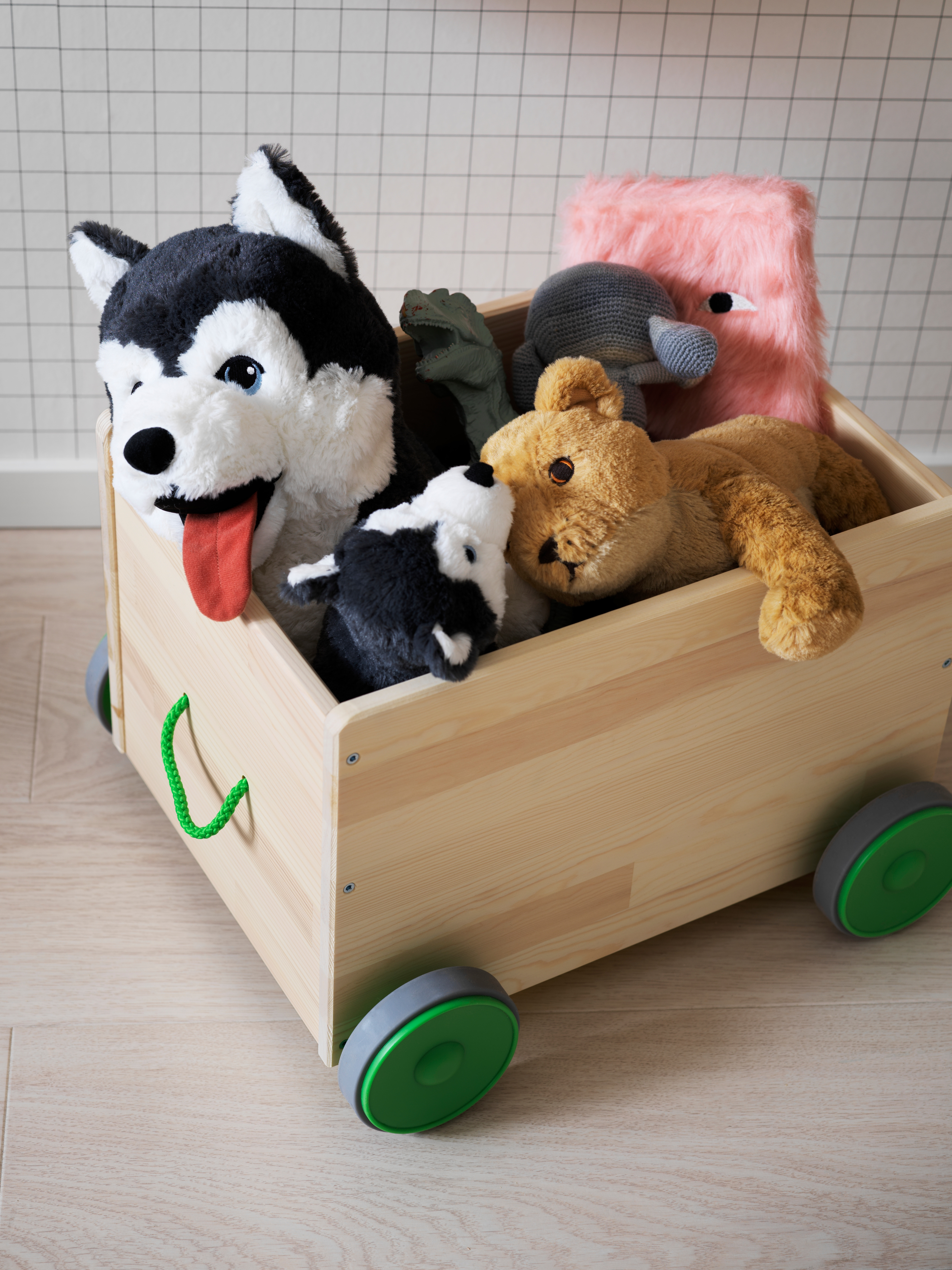 Toy storage box with four green wheels and green fabric handle, with three stuffed animal soft toys inside.