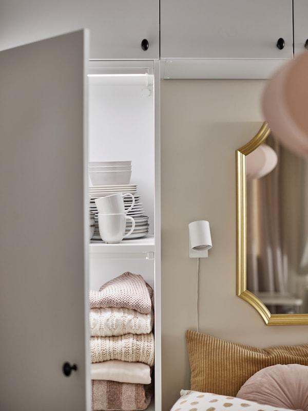 Egy fehér PLATSA gardróbrendszer az ágy mellett és fölött, az egyik ajtaja nyitva, ami látni engedi a szekrényben tárolt összehajtott pulóvereket és étkészleteket.