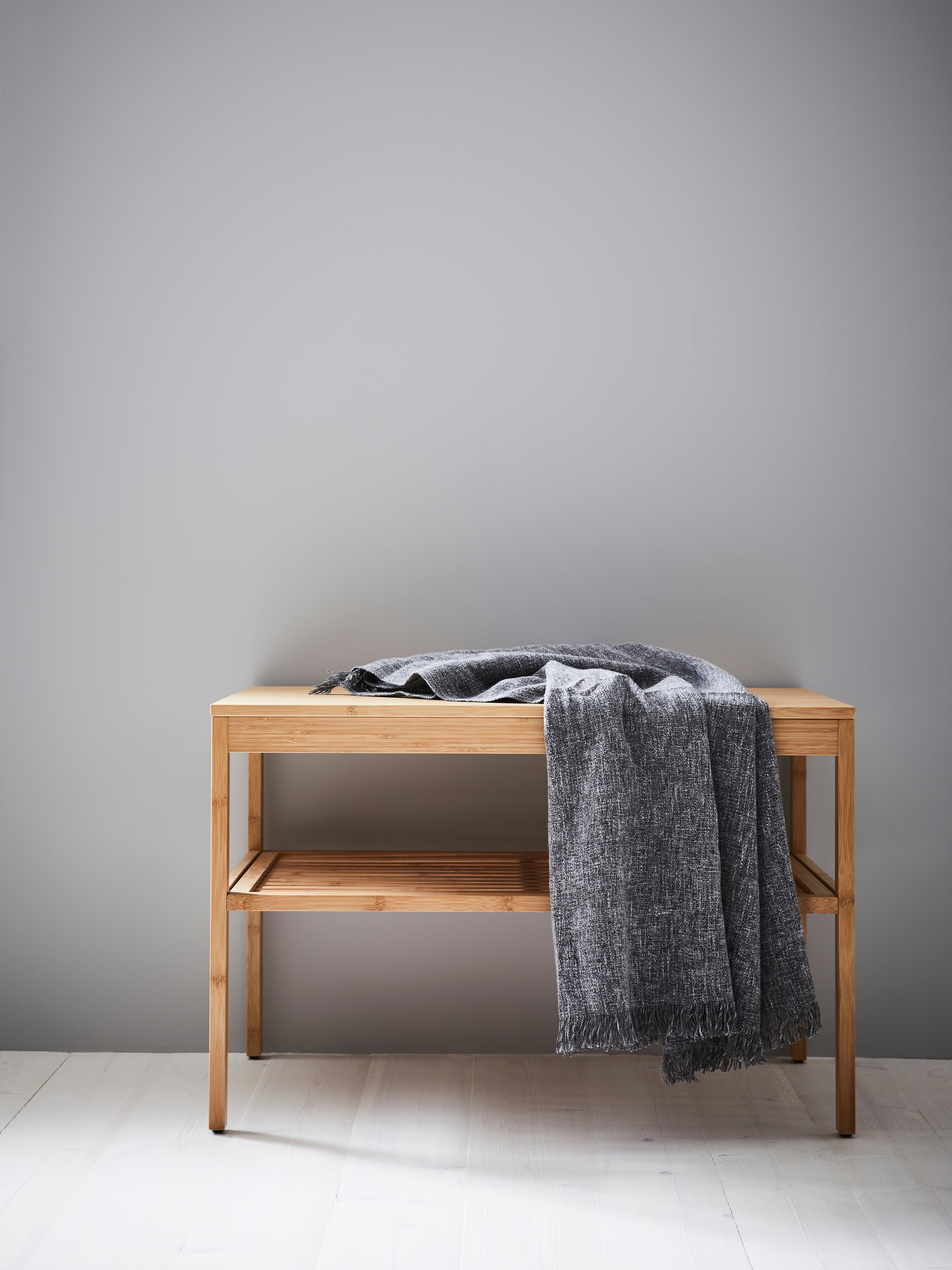 A rectangular, bamboo NORDKISA bench has a dark grey throw draped across it and stands against a grey wall on a wooden floor.