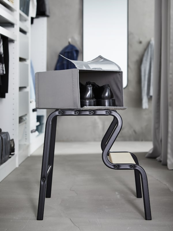 An open dark grey SKUBB shoe box containing a pair of black shoes placed on top of a black/birch GRUBBAN step stool.