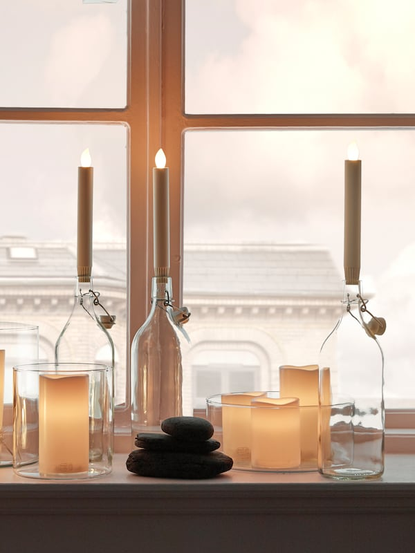 A window ledge, with three bottles with LED candles in them, and other LED candles and decorative objects.