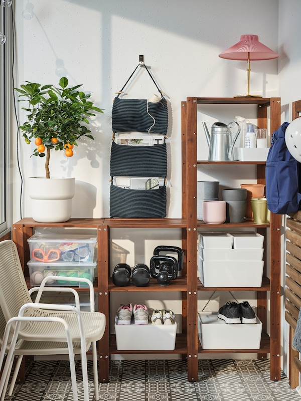 A spacious wooden shelving unit where storage boxes, plant pots and shoes are stored. Two chairs are stacked in front.