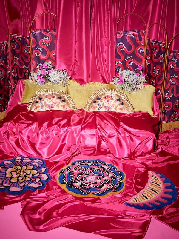 Ein 3er-Set mit bunten KARISMATISK Teppichen aus Wolle in Blumen- und Blattform liegt auf dem mit Satinstoff bedeckten Boden. Im Hintergrund sind goldfarbene Kissen zu sehen.