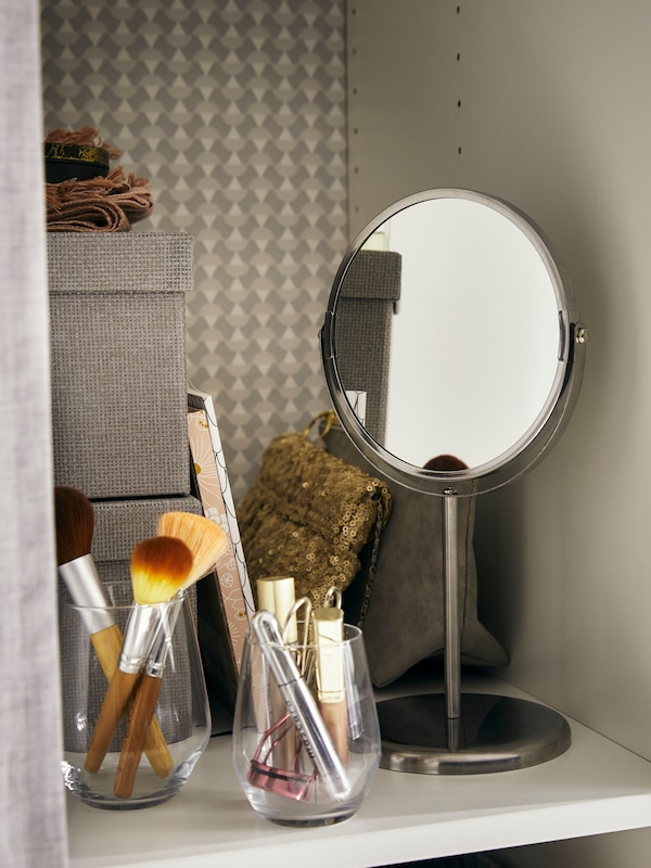 A small TRENSUM mirror sits on a shelf with KVARNVIK storage boxes and IVRIG glasses which hold make-up equipment.