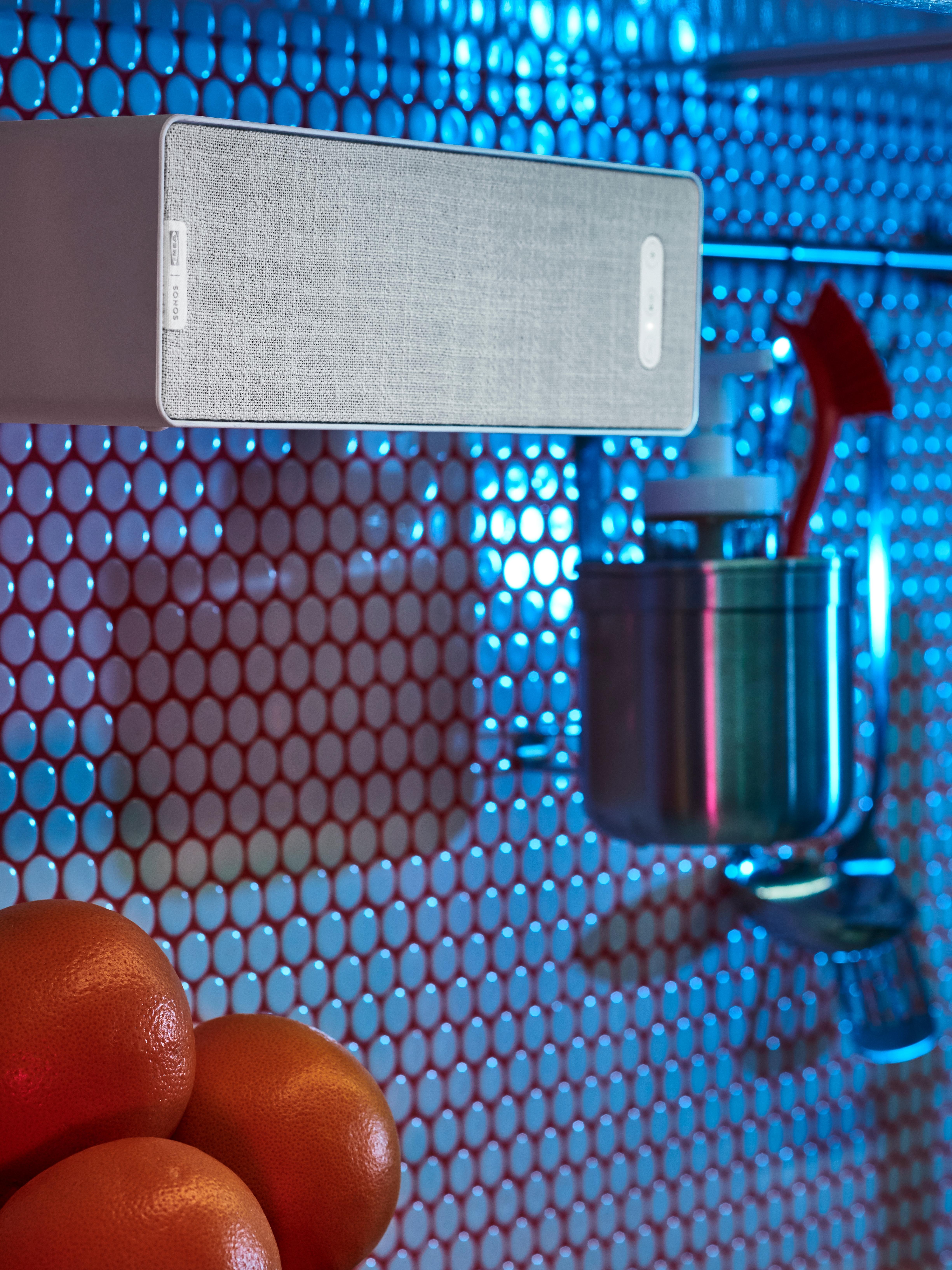 Beli SYMFONISK WiFi zvučnik polica visi na KUNGSFORS šini od nerđajućeg čelika na kuhinjskom zidu s okruglim pločicama.