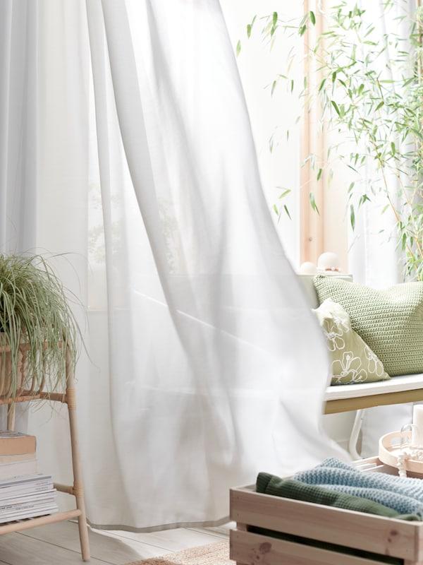 O cameră de zi luminoasă cu plante verzi și perne și o perdea GUNRID de culoare gri deschis, care se mișcă în vânt.