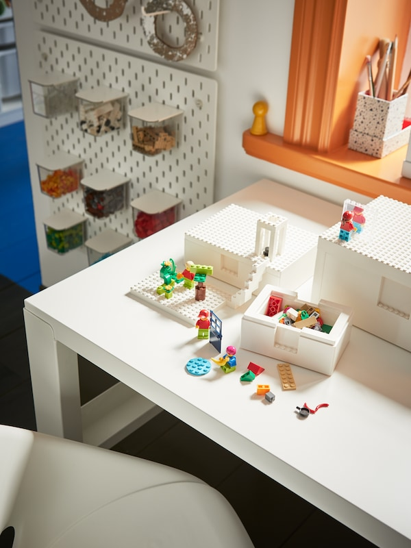 A white desk with white BYGGLEK LEGO® storage boxes with LEGO® figures in them and on the lids.
