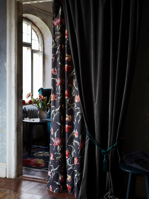 Grey SANELA curtains and black/floral pattern ROSENMOTT curtains positioned in a doorway between two rooms.