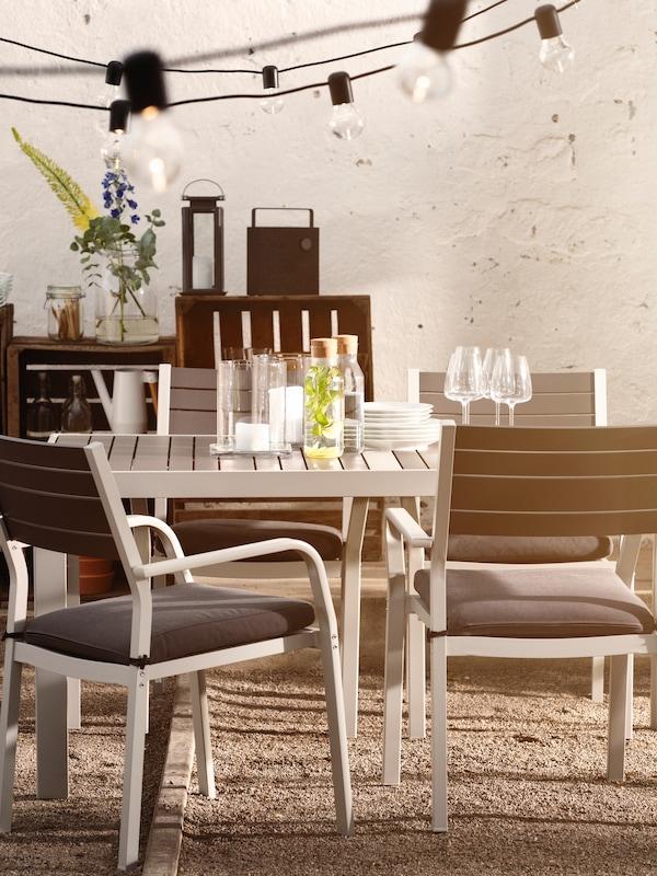 Zunanje pohištvo, med drugim miza, na kateri so kozarci, steklenice, krožniki in drugi predmeti, ter štirje stoli in viseče svetilke.