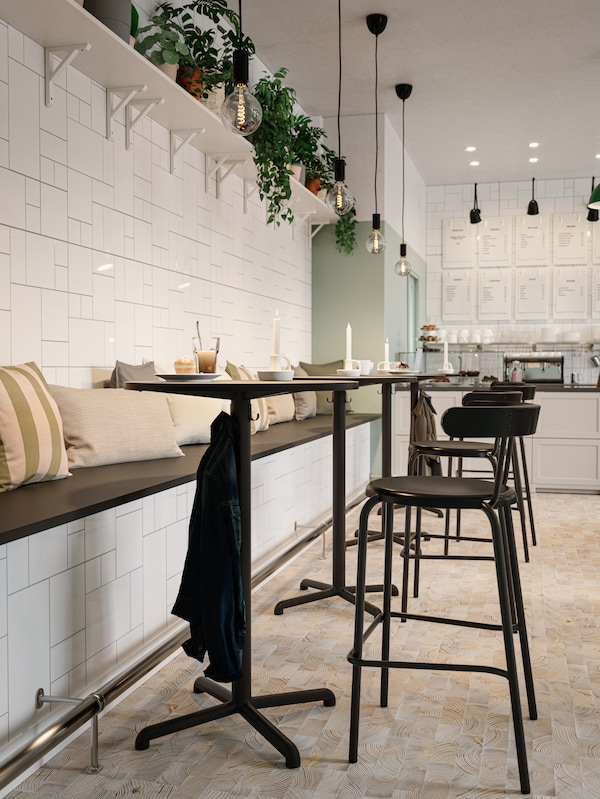 Tavoli e sedie da bar color antracite, panca in muratura piastrellata di bianco con cuscini beige, piante e lampade a sospensione.