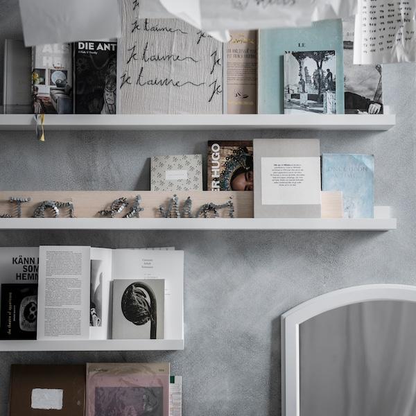 En MOSSLANDA tavelhylla ovanför en säng med konst, med en IKEA 365+ karaff med vatten och ett glas på.