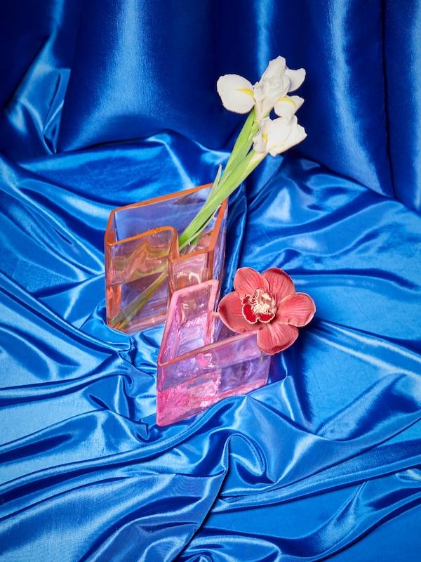 Das 2er-Set an KARISMATISK Vasen in Rosa ist so zusammengestellt, dass die Vasen den Buchstaben Z bilden. Sie stehen auf blauem Satinstoff. In ihnen befinden sich Blumen.