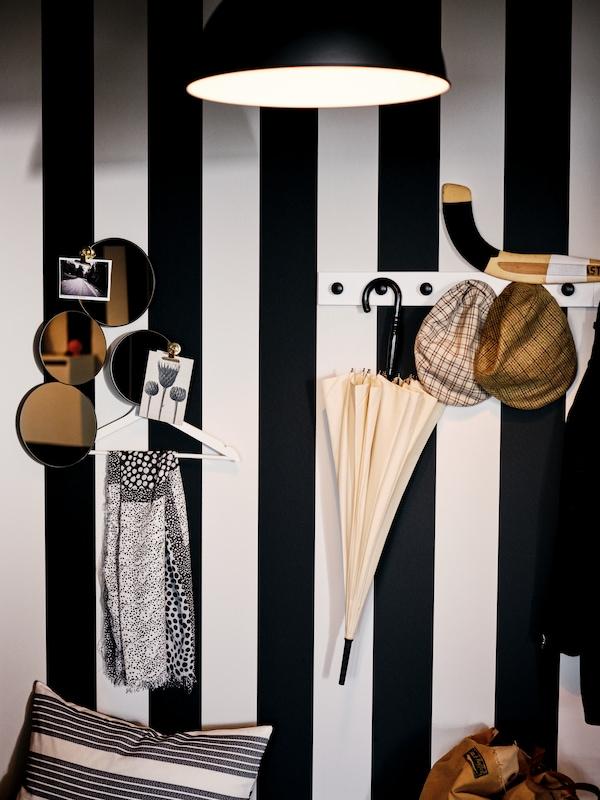 An einer in breiten Streifen schwarz und weiß gestrichenen Wand hängen verschiedene Gegenstände an schwarzen ENERYDA Knöpfen von einer weiß lasierten LURT Knopfleiste.
