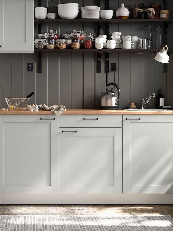 A grey KNOXHULT kitchen with dark grey panelled walls, shelving units stacked with jars, cups, bowls and plates.
