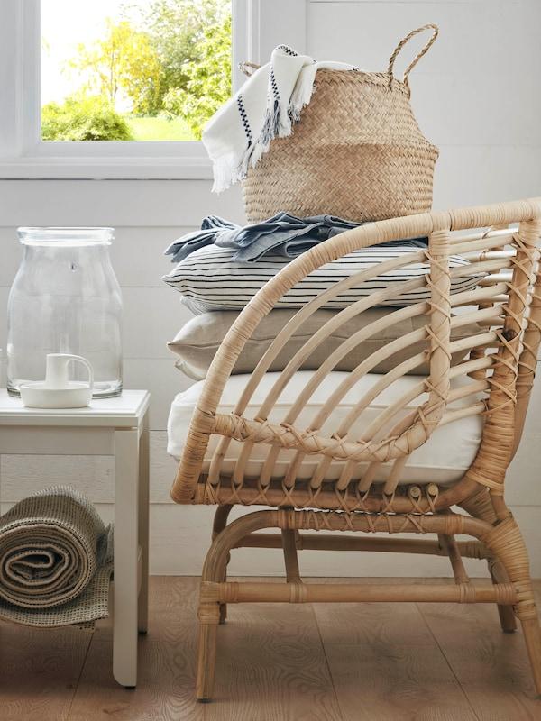 Un fauteuil en rotin avec un coussin confortable, quelques coussins supplémentaires en textile doux et un panier tout en haut.
