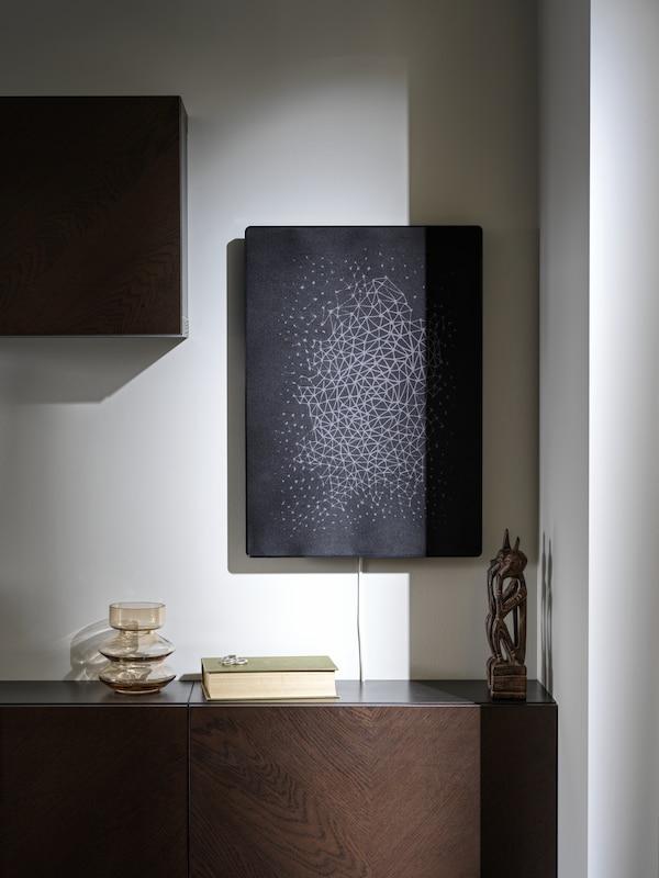 Sort SYMFONISK billedramme med WIFI-højttaler hænger på en væg og en hvid SYMFONISK billederamme med WIFI-højttaler