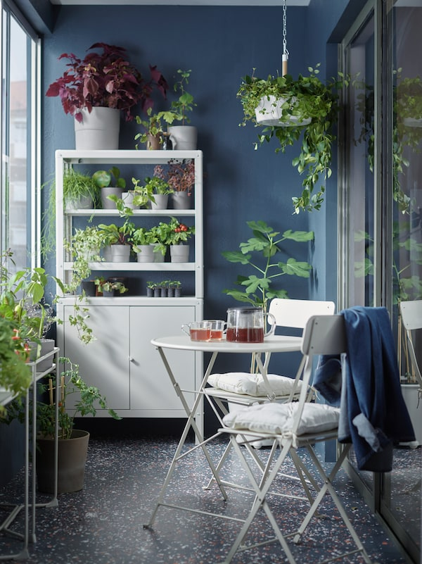 Balkon z bež mizo in dvema stoloma, bež elementi za shranjevanje z rastlinami in lonci za rastline ter viseča rastlina.