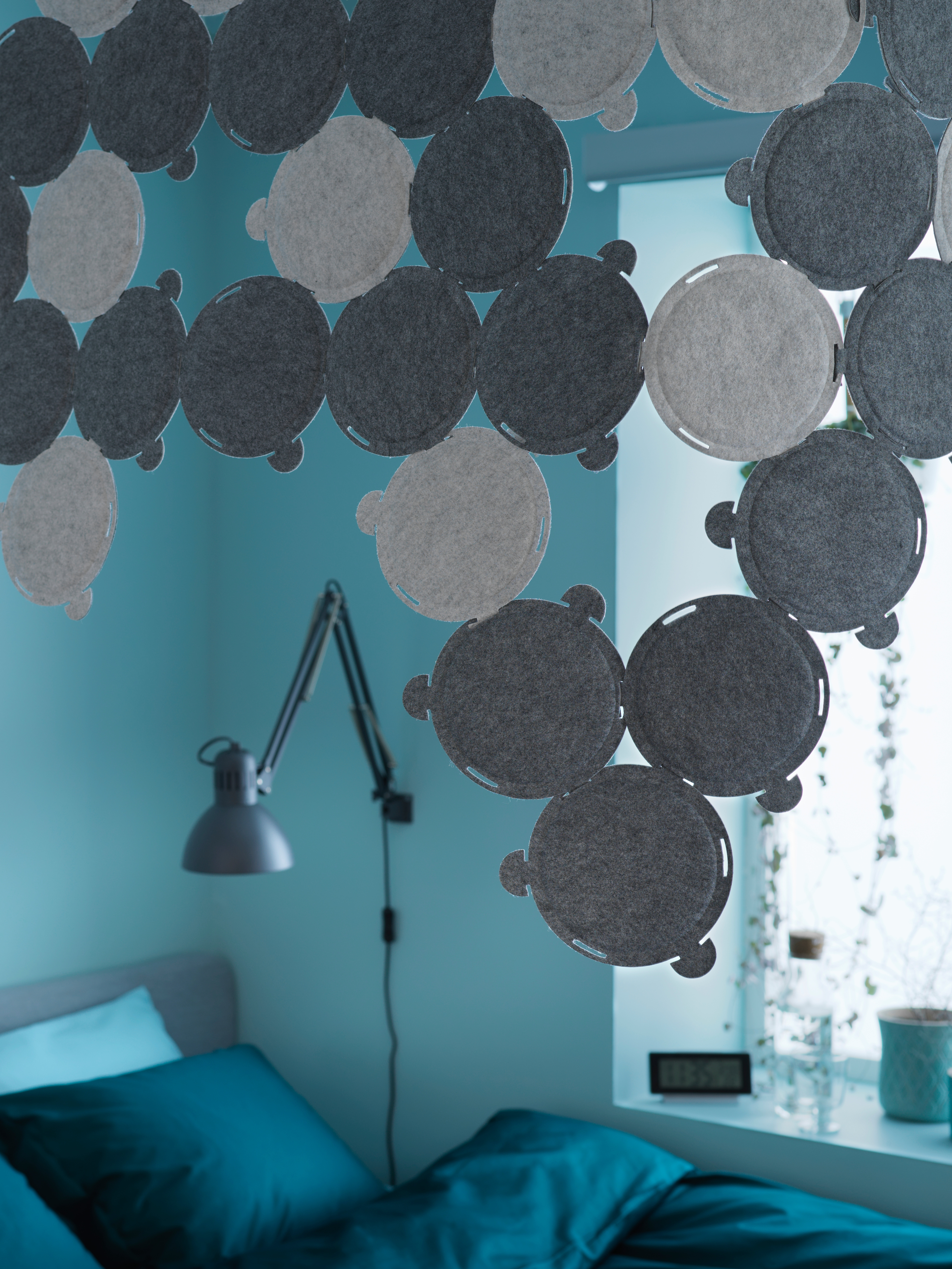 An ODDLAUG sound absorbent panel in grey, hanging in a bedroom with blueish-green walls containing a bed and reading lamp.