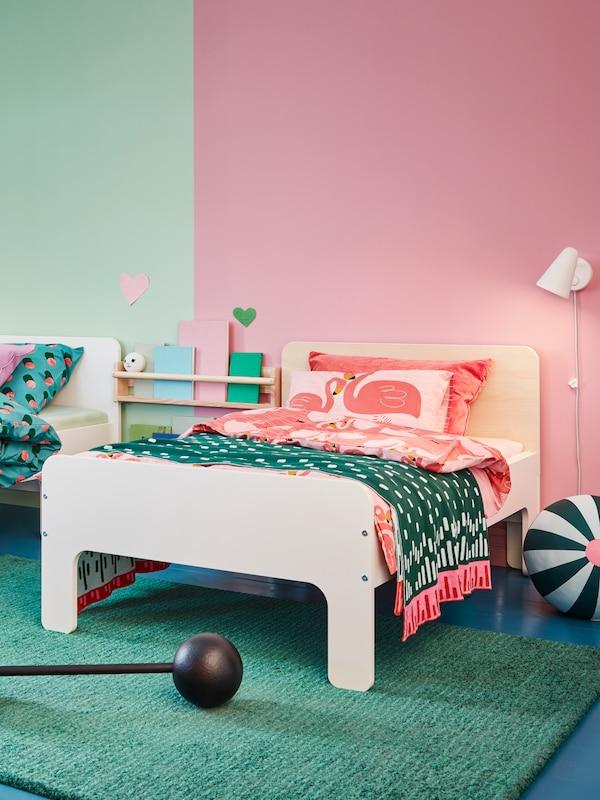 2 SLÄKT sengestel med forskellige sengegavle: En hvid og en af birk. Begge senge er redt med farvestrålende sengetøj.