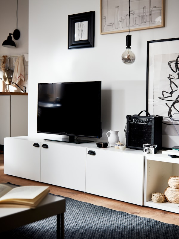 A low white BESTÅ storage combination with open cabinets and LAPPVIKEN doors holding a TV. A dark-gray MORUM rug is in front.