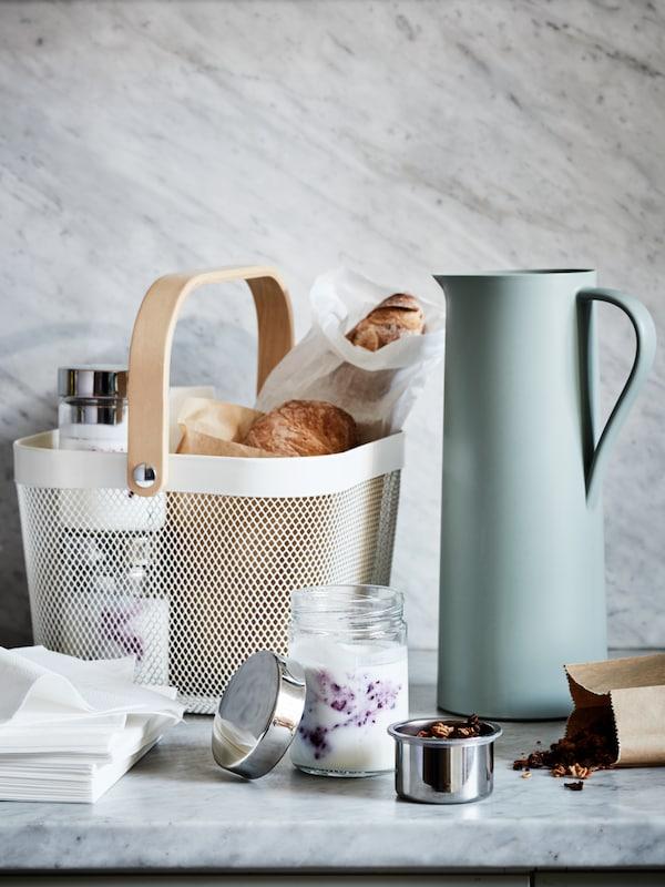 سطح عمل مع سلة RISATORP بها خبز ومرطبانات DAGKLAR بها زبادي وموسلي. يوجد ثرموس BEHÖVD على الجانب.
