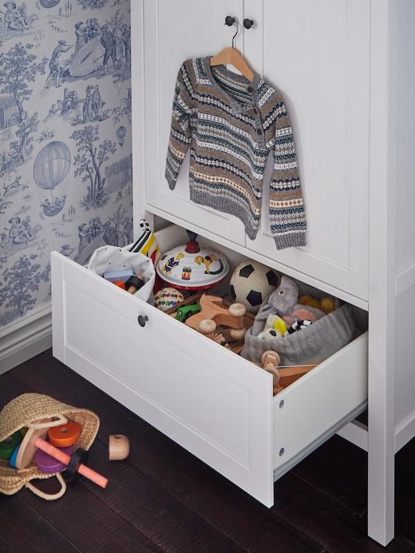 Hvidt garderobeskab, hvor den nederste skuffe er åben, så du kan se legetøjet indeni. En børnesweater hænger på skabsdørens knop.