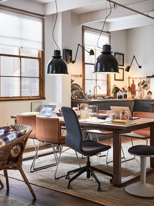 Salle à manger avec suspensions, table MÖRBYLÅNGA en plaqué chêne brun, chaises de bureau et chaises classiques.