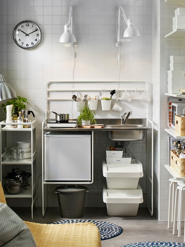 A white SUNNERSTA mini-kitchen against a white tiled wall, with two white lamps attached to the wall above it.