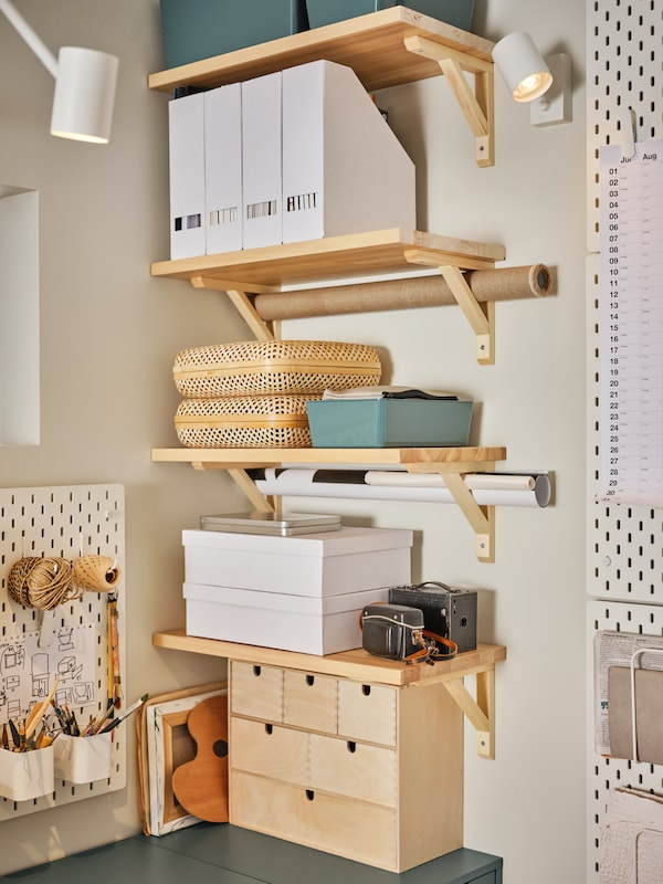 A close up of desk space neatly organized using wall shelves and desk accessories.