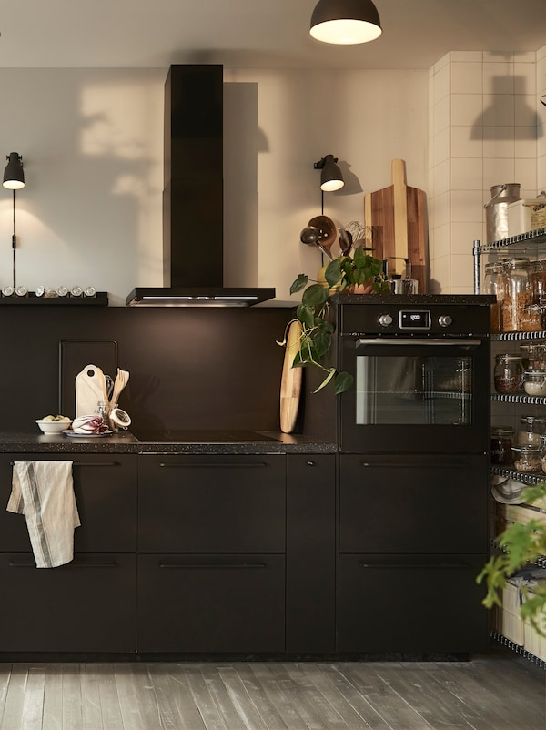 A black kitchen with a black extractor hood, a black built-in oven and a black mineral effect worktop.