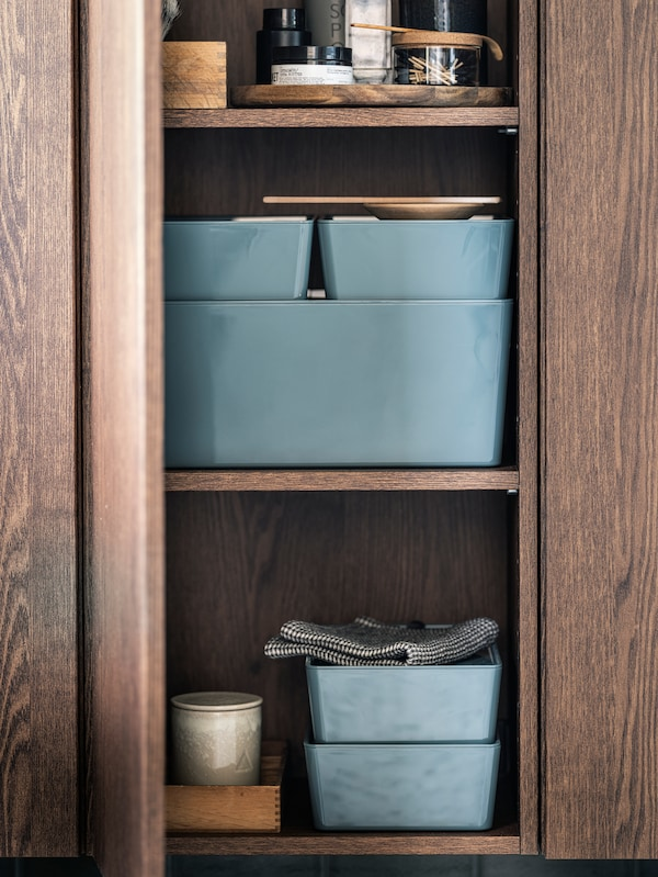 GODMORGON cabinet in wood with a half-open door, and KUGGIS storage boxes on its shelves.