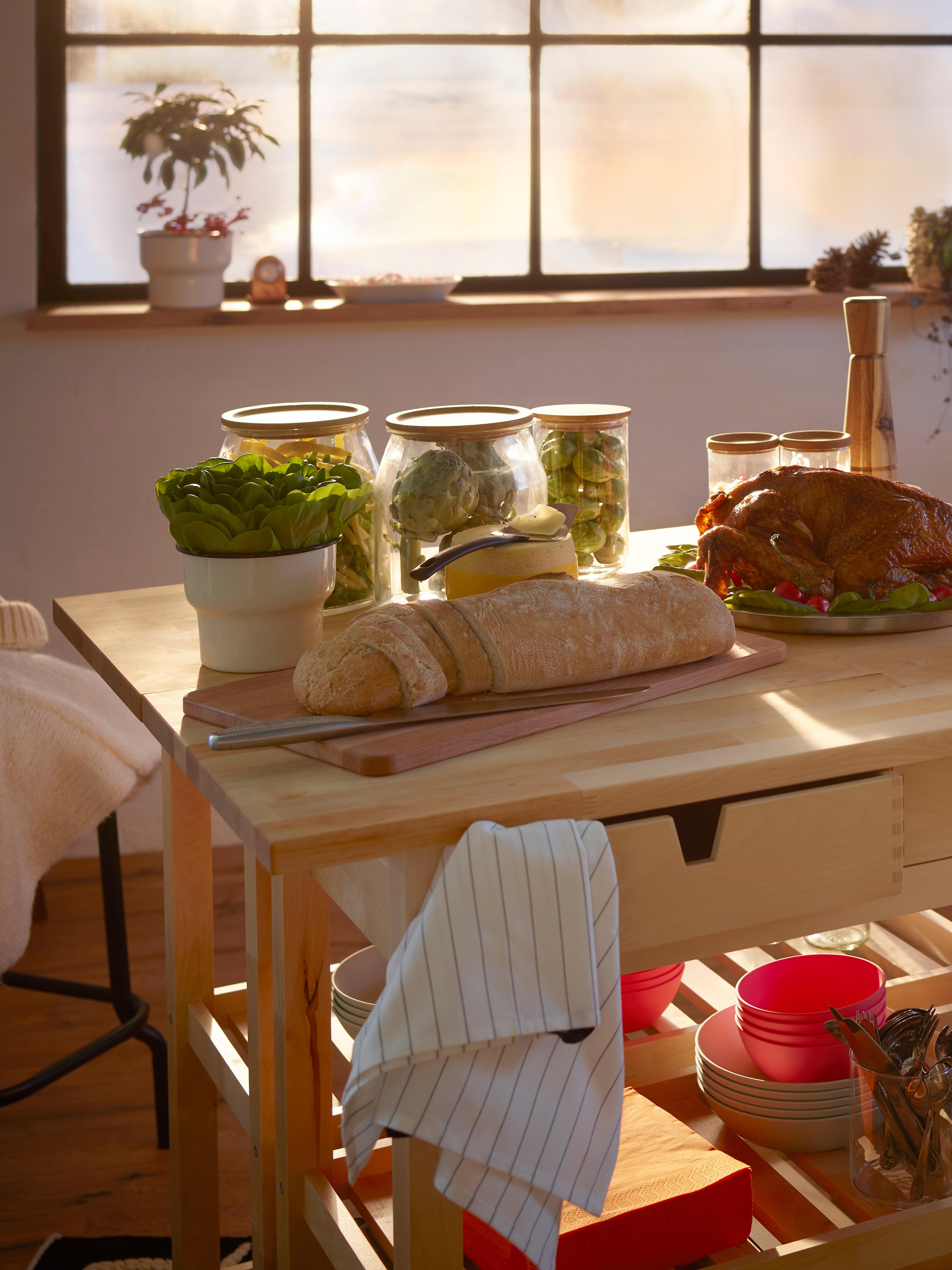 Due carrelli da cucina FÖRHÖJA in betulla massiccia affiancati per creare un'ampia area di servizio, con sopra vasetti ripieni di alimenti e una pagnotta.
