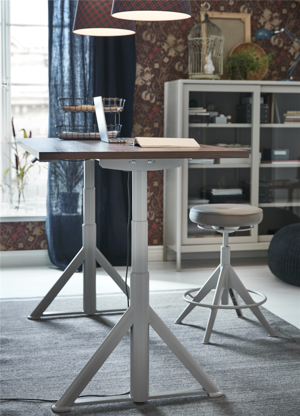 An IDÅSEN sit/stand desk in brown/beige on a grey rug in a room next to a window.
