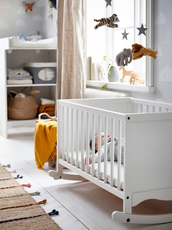 Un bebé tumbado en una cuna SOLGUL con colchón de espuma mirando hacia un móvil; está cerca de una ventana en una habitación luminosa.